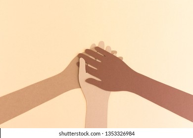 Paper cutout of different colored hands put together for image concept of diversity, teamwork, unity