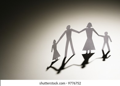 Paper cutout family of four standing holding hands.