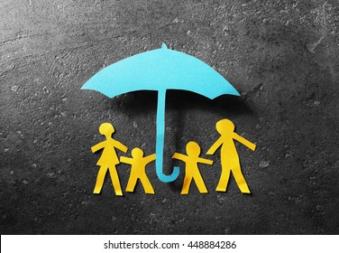 Paper cutout family of four under a blue paper umbrella