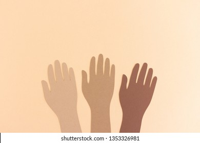Paper cutout of hands in diversity raised up