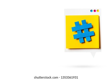 Paper cutout of hashtag symbol on a yellow speech bubble isolated. Concept of social media and digital marketing.