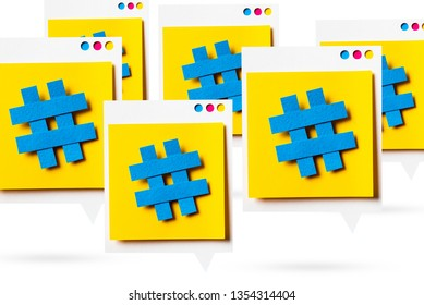 Paper cutout of hashtag symbols on a yellow speech bubble isolated white background. Concept of social media and digital marketing.