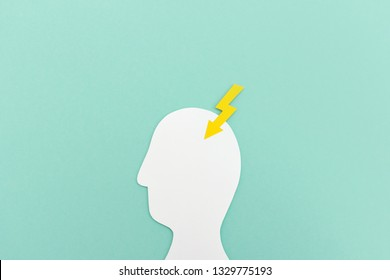Paper cutout of head silhouette with yellow lighting striking in head on blue background