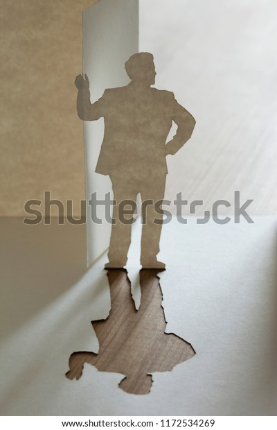 Paper cutout man standing holding door open, looking outside