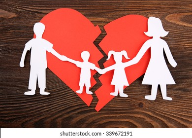 Paper cutout silhouette of a family split apart on a paper heart, divorce concept