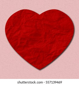 A paper cut-style crumpled red heart on pale pink background