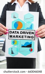 Paper with data driven marketing concept held by a businesswoman