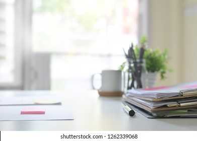 Paper document files and pen business equipment on office table and window light.