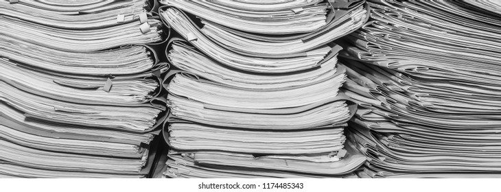 Paper documents stacked in archive. Documents on the shelves of archive room. Office shelves in the closet full of files. black and white photo