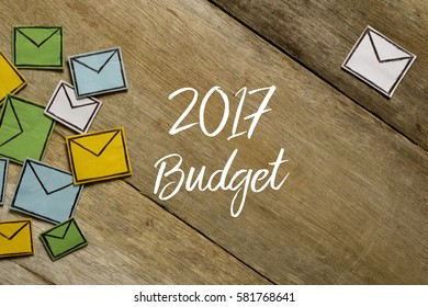 Paper envelopes and 2017 BUDGET written on wooden background.