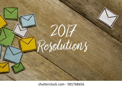 Paper envelopes and 2017 RESOLUTIONS written on wooden background.