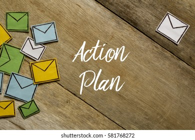 Paper envelopes and ACTION PLAN written on wooden background.