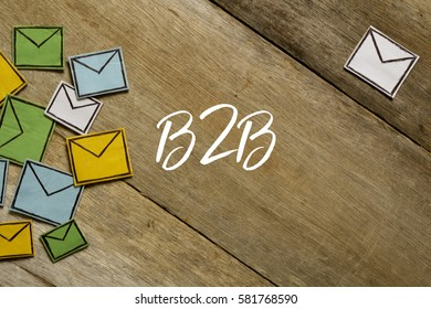Paper envelopes and B2B written on wooden background.