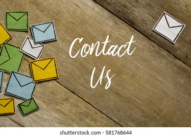 Paper envelopes and CONTACT US written on wooden background.