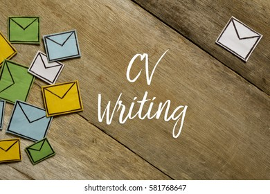 Paper envelopes and CV WRITING written on wooden background.
