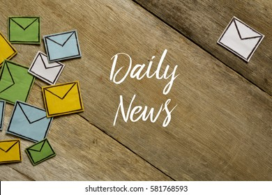 Paper envelopes and DAILY NEWS written on wooden background.