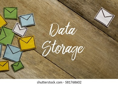 Paper envelopes and DATA STORAGE written on wooden background.