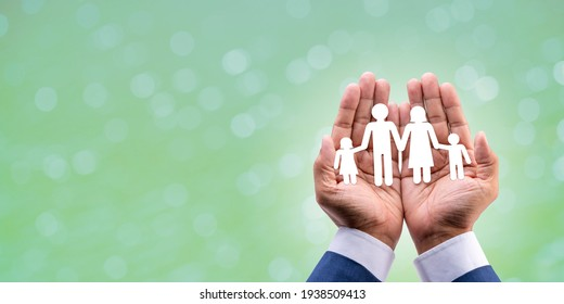 Paper of family in cupped hands on blur green background, for financial, health, security and care concept.
