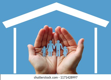 Paper family in hands with home on blue background welfare concept