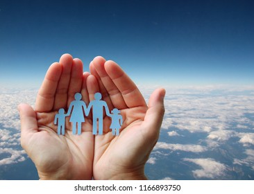 Paper family in hands on aerial sky view background