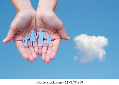 Paper family in hands on blue sky background welfare concept