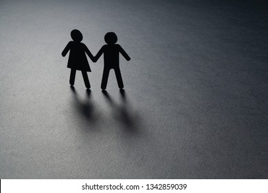 Paper figure of a couple holding hands on gray surface. Loneliness, childless, old age concept.