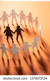 Paper figure of a couple surrounded by circle of paper people holding hands on red surface. Minorities, bulling, diversity concept.