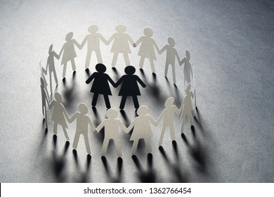 Paper figure of female couple surrounded by circle of paper people holding hands on gray surface. Minorities, bulling, diversity concept.