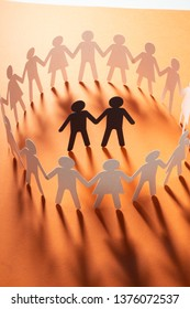 Paper figure of male couple surrounded by circle of paper people holding hands on orange surface. Minorities, bulling, diversity concept.