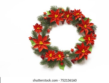 Paper flower poinsettia and spruce branches. Christmas wreath. White background. Colors are green, red, yellow.