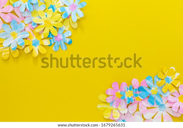 Paper flowers composition. Pink, yellow and blue flowers on a bright yellow background.  Mother's Day concept. Flat lay, top view, copy space