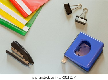 Paper folders, black stapler, black paper clips and blue paper puncher on blue background. Green, yellow, red paper folders