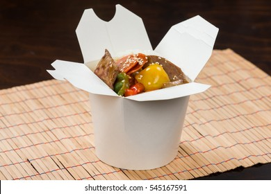 Paper food box with meat, vegetables and rice korean style on bamboo mat