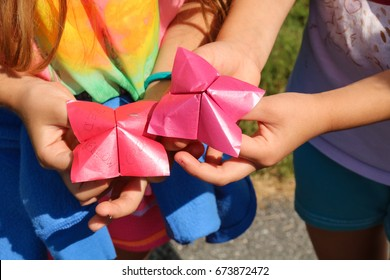 A paper fortune teller is a form of origami used in children's games. There are two pink fortune tellers held by two girls. The fortune teller game is popular at summer camps, sleep overs, or recess.
