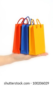 Paper gift bags in hand of a woman