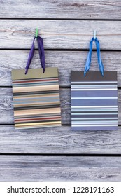 Paper gift bags hanging on wire with clothespins. Two colour packages hang on clothesline with clothespins on rustic wooden background.