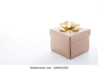 Paper gift box with golden ribbon on white background