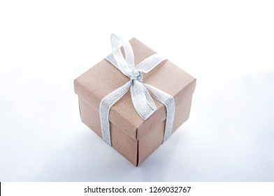 Paper gift box with silver ribbon on white background