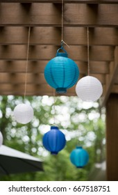 Paper globe lights under an outdoor pergola add a festive touch to outdoor entertaining.