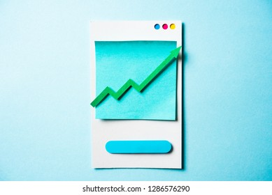 Paper green arrow growing up on smartphone and blue background. Growth business graph chart, stock market investment trading and trends concept.