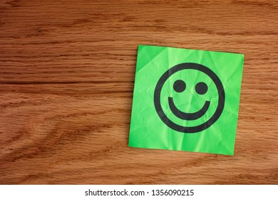 Paper with happy face on wooden background. Close up.