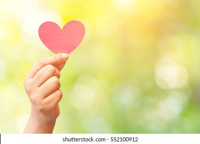 paper heart in hand on abstract nature background.