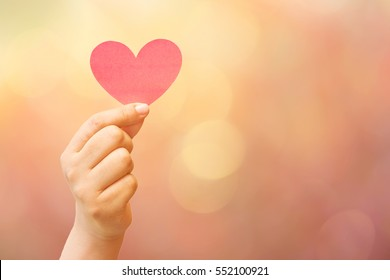 paper heart in hand on colorful blurred bokeh background with retro effect