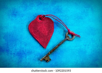 Paper Heart & Key in the Centre of a Blue Grunge Background