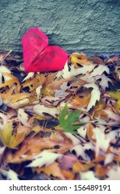 a paper heart in a pile of leaves