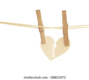 paper heart torn hanging on rope and white background