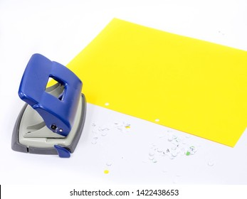 paper hole puncher and yellow paper of office stationery on white background