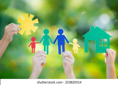 Paper house and family in hands against spring green background. Real estate business concept