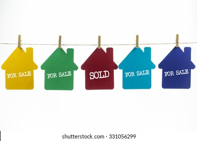 Paper house hanging on a rope with a word For Sale and Sold