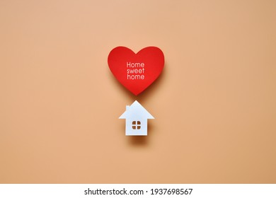 A paper house, a heart, and the inscription: sweet home. A symbol of protection and care for the home and family
